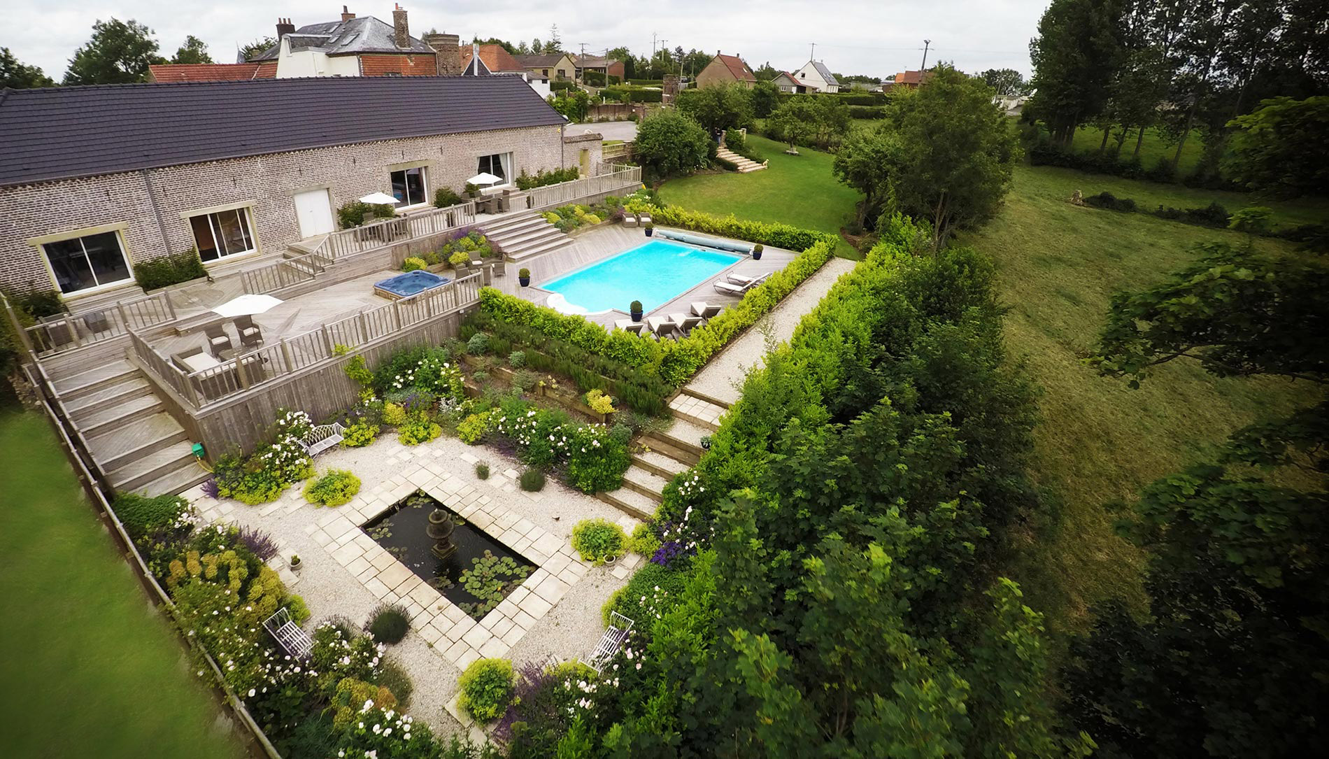 Luscious flowering garden with outdoor heated swimming pool, jacuzzi, Koi pond and lawn area big enough for Marquees. Outdoor access to Gym and Sauna from decking area and courtyard